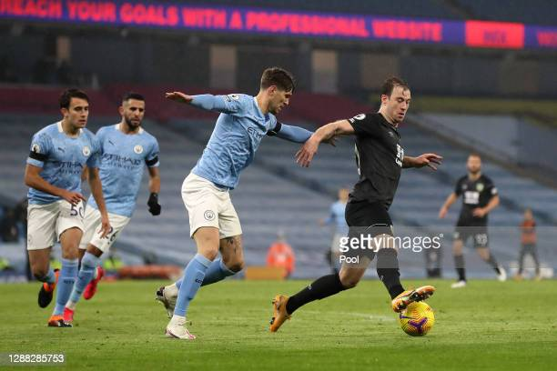 Ashley Barnes of Burnley is challenged by John Stones of Manchester City during the Premier League match between Manchester City and Burnley at...