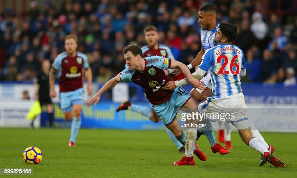 Ashley Barnes of Burnley is tackled by Christopher Schindler of Huddersfield Town during the Premier League match between Huddersfield Town and...