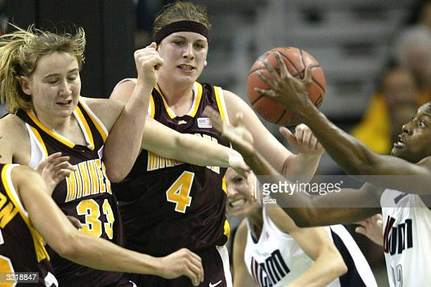 Ashley Battle of the University of Connecticut Huskies fights for the ball against Jamie Broback and Janel McCarville of the Minnesota Golden Gophers...