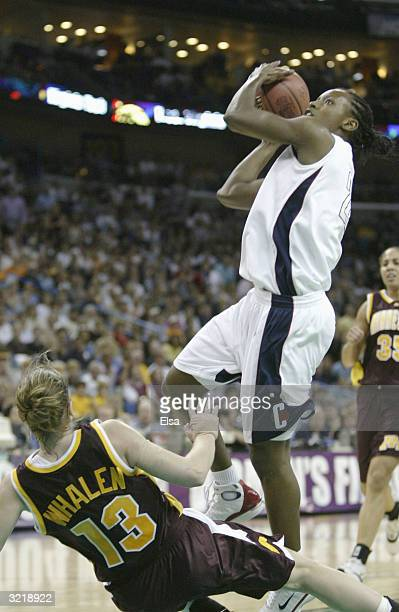 Ashley Battle of the University of Connecticut Huskies shoots over the defense of Lindsay Whalen of the Minnesota Golden Gophers during the semifinal...