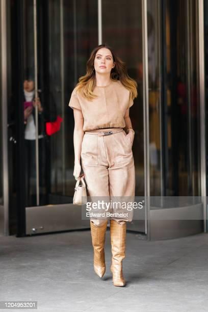 Ashley Benson wears a light brown suede t-shirt, a belt, pants, brown crocodile pattern boots, a bag, outside Longchamp, during New York Fashion Week...