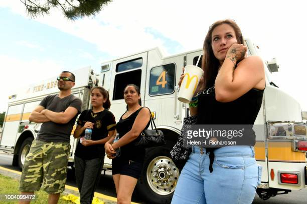 Ashley Bering right and other Westbury Apartment residents watch as firefighters continue to fight fire at the scene of a deadly apartment complex...