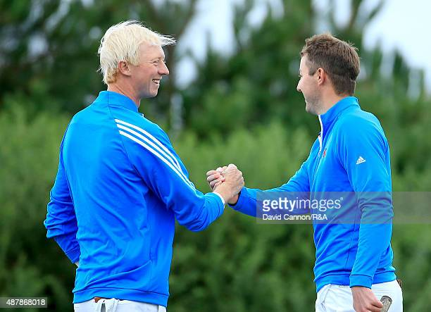 Ashley Chesters and Jimmy Mullen of Great Britain and Ireland celebrate on the 16th green after they had won their match by 32 against Maverick...