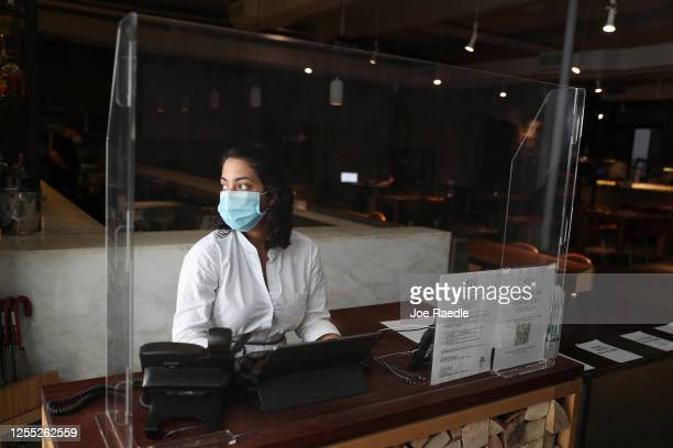Ashley Clinton the hostess waits for customers behind a plexiglass partition at the KYU restaurant in Wynwood on July 09 2020 in Miami Florida The...