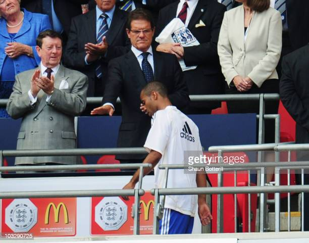 Ashley Cole of Chelsea walks past England manager Fabio Capello as he collects his medal after defeat in the FA Community Shield match between...