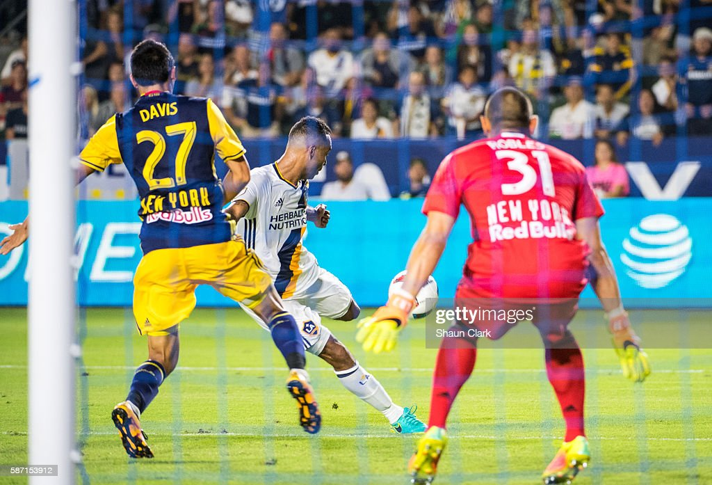 Ashley Cole #3 of Los Angeles Galaxy scores a goal as Sean Davis #27 and Luis Robles #31 of New York Red Bulls defend during Los Angeles Galaxy's MLS match against the New York Red Bulls at the StubHub Center on August 7, 2016 in Carson, California. The match ended 2-2