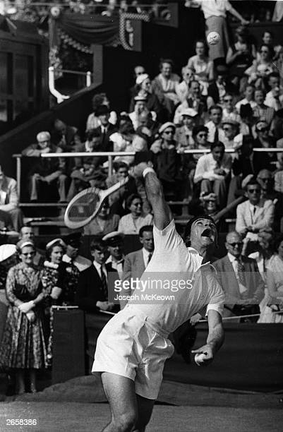 Ashley Cooper of Australia in action serving during a match at the Wimbledon Lawn Tennis Championships. Original Publication: Picture Post - 8544 -...