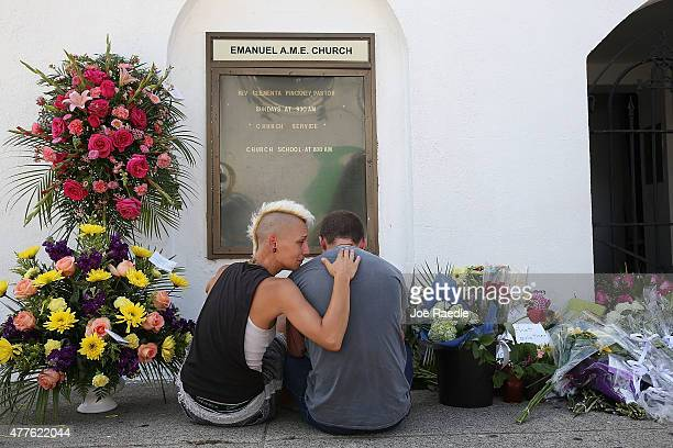 Ashley Edge and Brad Hutchinson pay their respects in front of Emanuel AME Church on June 18, 2015 in Charleston, South Carolina. Nine people were...