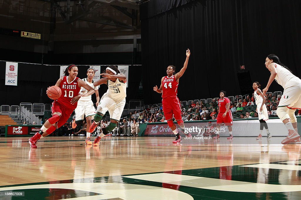 Ashley Eli #10 of the North Carolina State Wolfpack drives to the basket past Macy Keen #31 of the Miami Hurricanes on December 20, 2012 at the BankUnited Center in Coral Gables, Florida. The Hurricanes defeated the Wolfpack 79-53.
