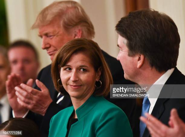 Ashley Estes smiles at her husband newly swornin Associate Justice of the US Supreme Court Brett Kavanaugh while US president Donald Trump applauds...