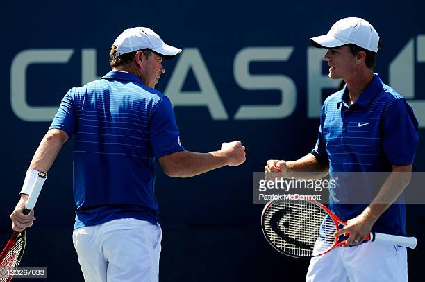 Ashley Fisher of Australia and Stephen Huss of Australia bump fists during their doubles match against Martin Emmrich of Germany and Andreas...