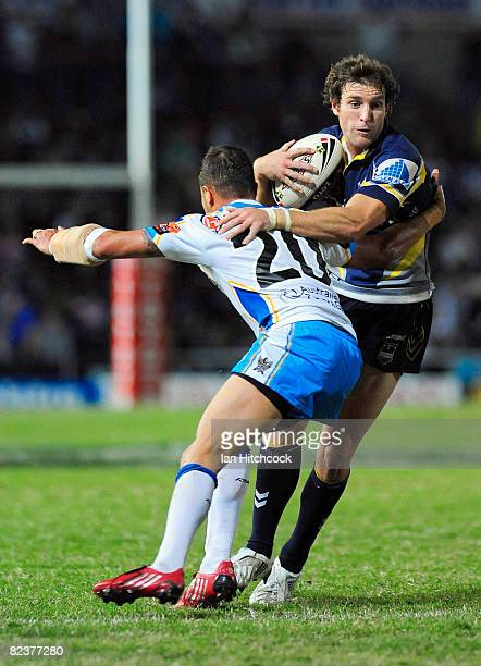 Ashley Graham of the Cowboys is tackled by Scott Prince of the Titans during the round 23 NRL match between the North Queensland Cowboys and the Gold...