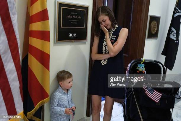 Ashley Harper former campaign staffer for the late US Sen John McCain pays respect with her son Fincher outside McCain's office at Russell Senate...
