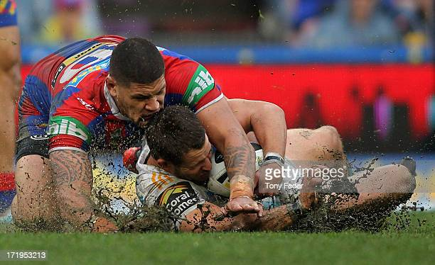 Ashley Harrison of the Titans is tackled by Willie Mason during the round 16 NRL match between the Newcastle Knights and the Gold Coast Titans at...