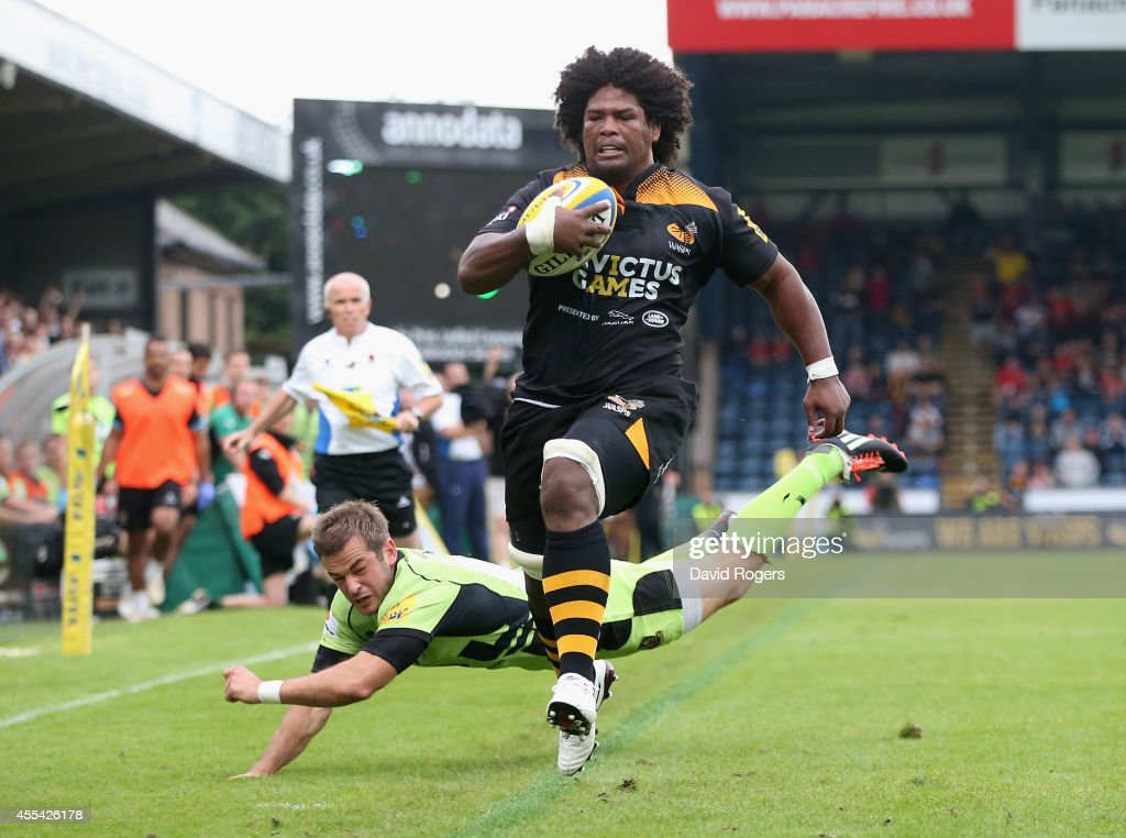 Ashley Johnson of Wasps breaks away from Stephen Myler to score the first try during the Aviva Premiership match between Wasps and Northampton Saints at Adams Park on September 14, 2014 in High Wycombe, England.