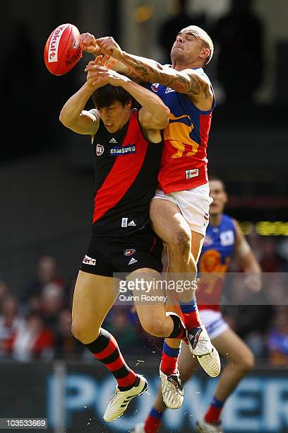 Ashley McGrath of the Lions spoils a mark by Angus Monfries of the Bombers during the round 21 AFL match between the Essendon Bombers and the...
