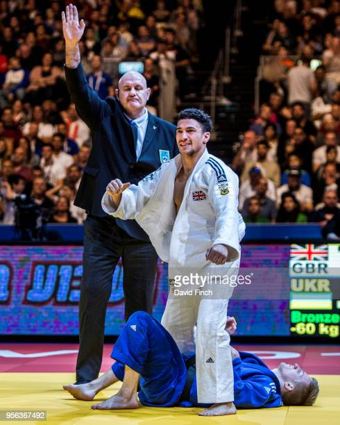 Ashley McKenzie of Great Britain happily rises to his feet after holding Artem Lesyuk of the Ukraine for an ippon to win the u60kg bronze medal...