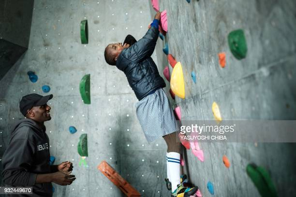 TOPSHOT Ashley Muthoni challenges bouldering on the artificial climbing wall during a weeklong free climbing training for visually impaired and blind...