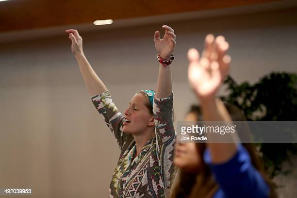 Ashley Nickel raises her arm as she prays with others in the congregation from Abundant Life United Pentecostal church for the city of Moore before...