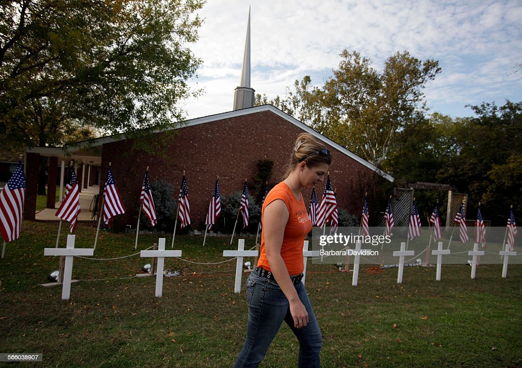 Ashley Norris walks away from a temporary memorial site setup in front of the Central Christian Chu : News Photo