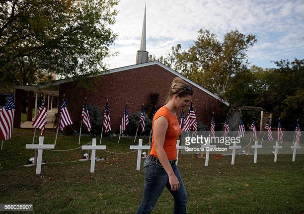 Ashley Norris walks away from a temporary memorial site setup in front of the Central Christian Church in memory of those killed and wounded at Fort...