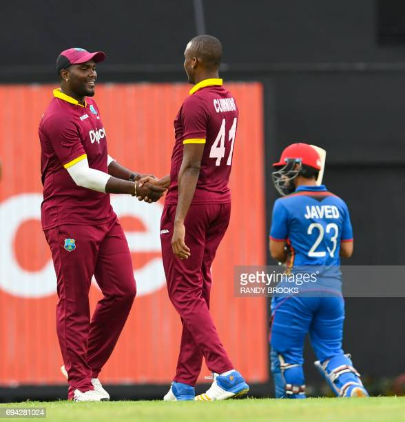 Ashley Nurse and Miguel Cummins of West Indies celebrate the dismissal of Javed Ahmadi of Afghanistan during the 1st ODI match between West Indies...
