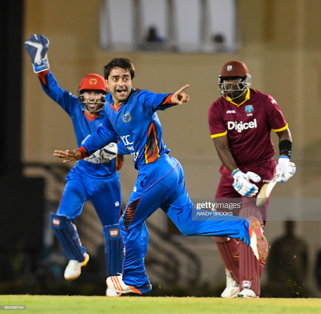 Ashley Nurse (R) of West Indies is dismissed by lbw by Rashid Khan (L)of Afghanistan during the 1st ODI match between West Indies and Afghanistan at Darren Sammy National Cricket Stadium, Gros Islet, St. Lucia, June 09, 2017. / AFP PHOTO / Randy Brooks