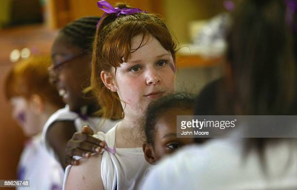 Ashley Potts stands with fellow homeless children while practicing a dance routine for a talent show on June 20, 2009 in Dallas, Texas. She was...
