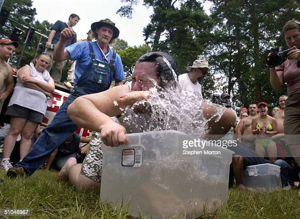 Ashley Richardson the returning Bobbing For Pig's Feet champion pulls out a pig's foot during the 9th Annual Summer Redneck Games July 10 2004 in...
