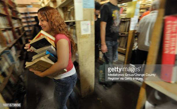 USA Ashley Trigg tries to navigate the small aisles at Acres of Books as she carries her books in Long Beach CA on July 10 2010 The ArtExchange who...