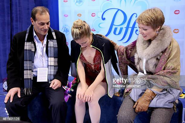 Ashley Wagner with her coaches Rafael Arutyunyan and Nadia Kanaeva waits for her scores in the kiss and cry after skating in the ladies free skate...