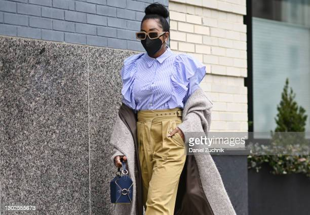 Ashley Weddington is seen wearing a blue striped blouse, brown pants, gray coat, blue purse and brown sunglasses outside the Rebecca Minkoff show...