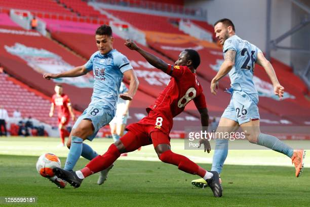 Ashley Westwood and Phil Bardsley of Burnley battle for the ball with Naby Keita of Liverpool during the Premier League match between Liverpool FC...