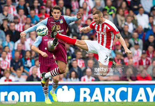 Ashley Westwood of Aston Villa is challenged by Phil Bardsley of Stoke City during the Barclays Premier League match between Stoke City and Aston...