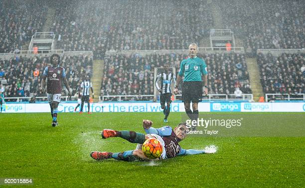 Ashley Westwood of Aston Villa slides across the wet grass to put the ball out of play during the Barclays Premier League match between Newcastle...