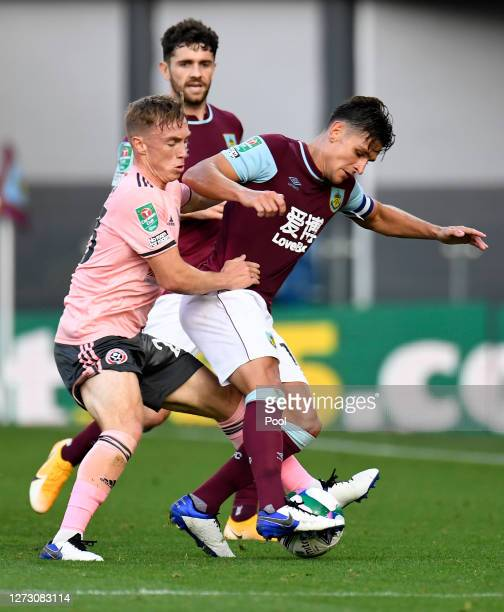 Ashley Westwood of Burnley battles for possession with Ben Osborn of Sheffield United during the Carabao Cup second round match between Burnley and...