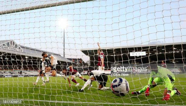 Ashley Westwood of Burnley scores their side's first goal past Tosin Adarabioyo and Alphonse Areola of Fulham during the Premier League match between...