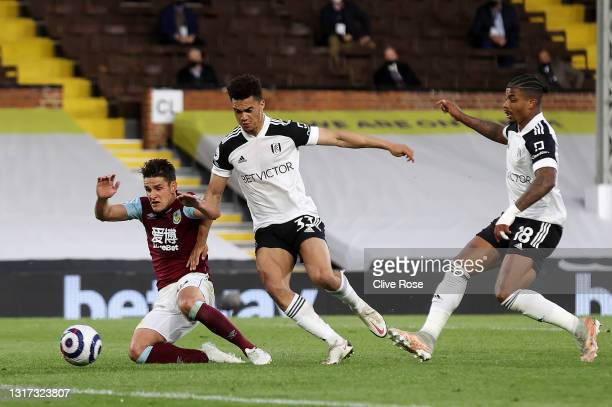 Ashley Westwood of Burnley scores their team's first goal under pressure from Antonee Robinson of Fulham during the Premier League match between...