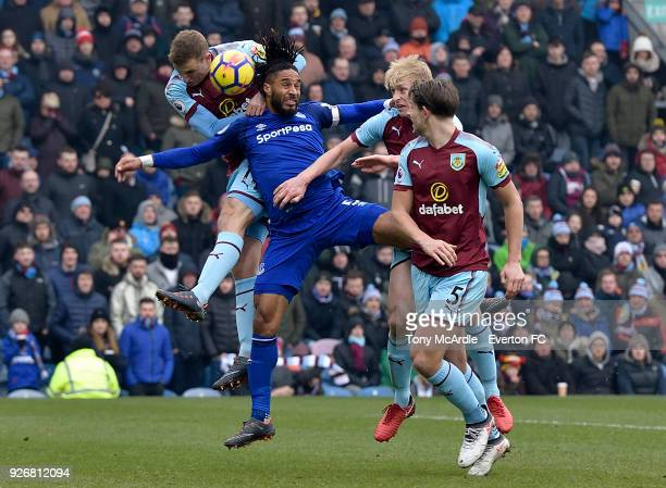 Ashley Williams of Everton challenges for the ball with Chris Wood Ben Mee and James Tarkowski of Burnley during the Premier League match between...