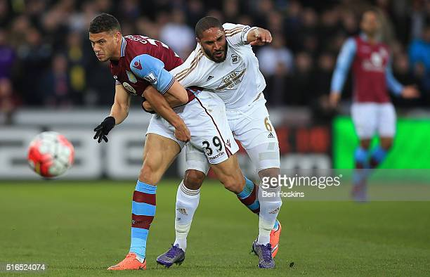 Ashley Williams of Swansea City and Rudy Gestede of Aston Villa compete for the ball during the Barclays Premier League match between Swansea City...
