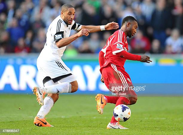 Ashley Williams of Swansea City and Stephane Sessegnon of West Bromwich Albion chase the ball during the Barclays Premier League match between...