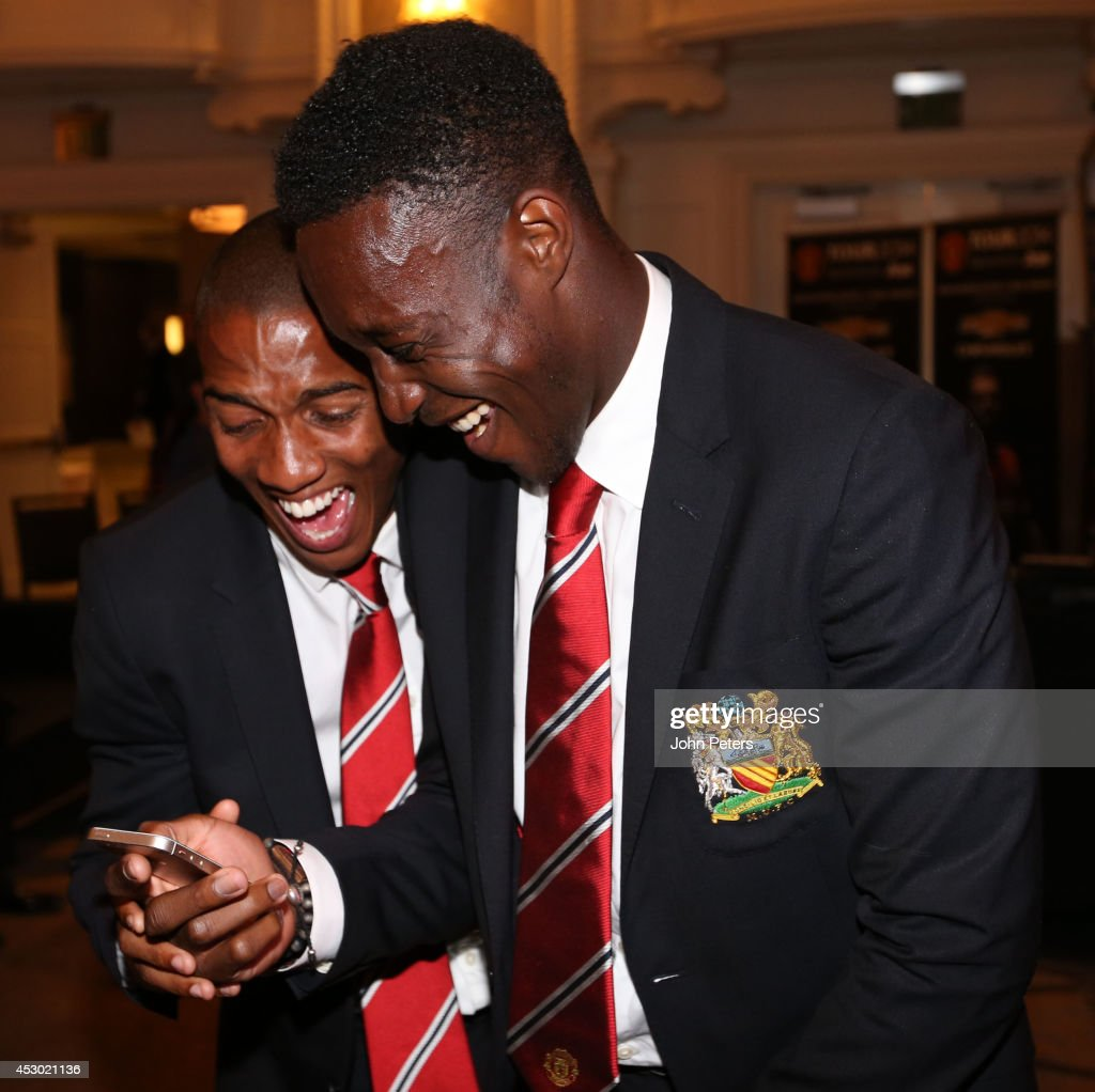 Ashley Young and Danny Welbeck of Manchester United laugh as they look at their phone as they arrive in Detroit as part of their pre-season tour of the United States on July 31, 2014 in Detroit, Michigan.