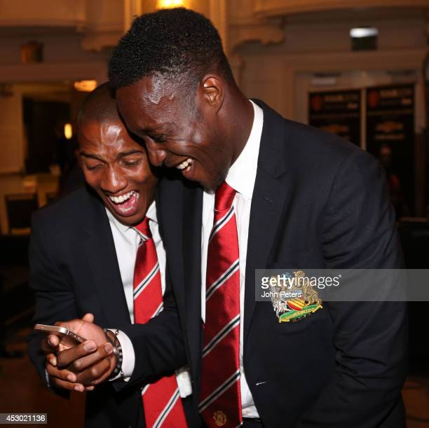 Ashley Young and Danny Welbeck of Manchester United laugh as they look at their phone as they arrive in Detroit as part of their preseason tour of...