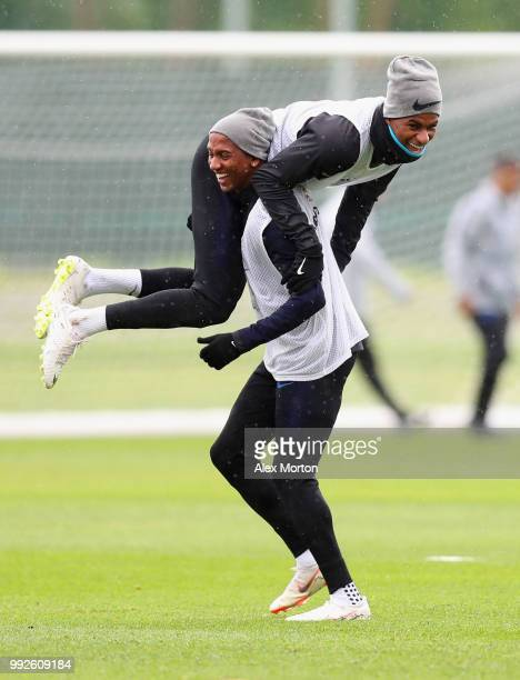 Ashley Young carries team mate Marcus Rashford as they joke during an England training session at Spartak Zelenogorsk Stadium on July 6 2018 in Saint...