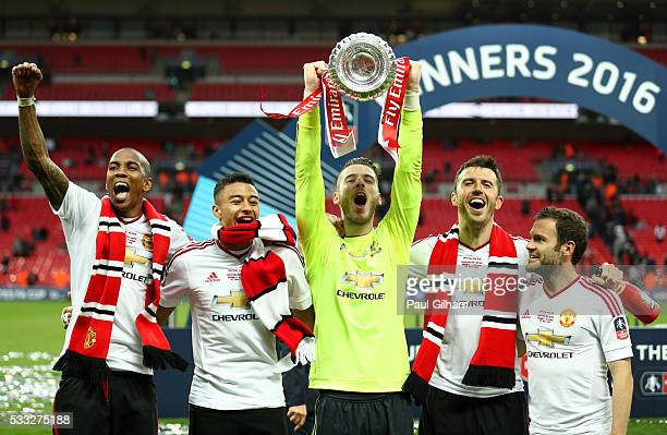 Ashley Young Jesse Lingard David De Gea Michael Carrick and Juan Mata of Manchester United celebrate with the trophy on the pitch after The Emirates...