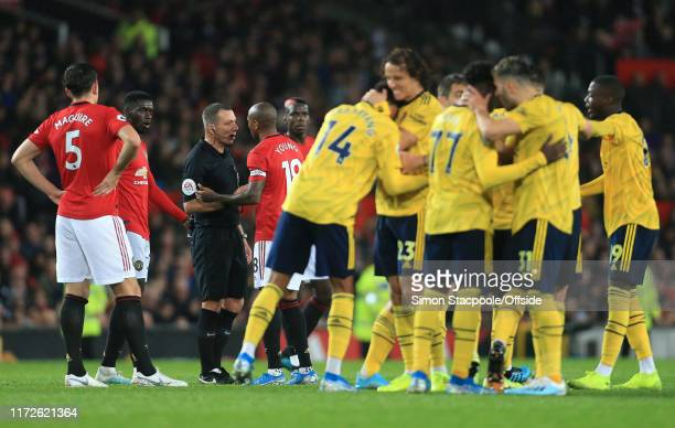 Ashley Young of Man Utd argues with referee Kevin Friend over the VAR decision as Arsenal celebrate their allowed equalising goal during the Premier...