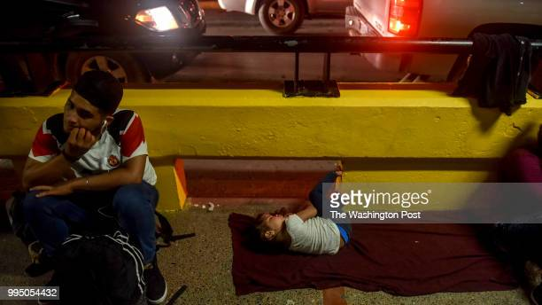 Ashly from Honduras rests next to her father Oscar left as they camp next to a US Customs checkpoint on the Gateway International Bridge on Saturday...
