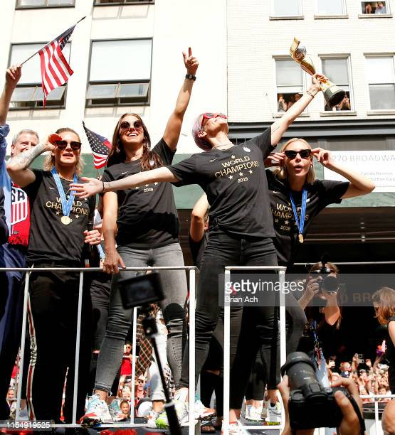 Ashlyn Harris Alex Morgan and Allie Long stand with Megan Rapinoe as she poses with the trophy during the US Women's National Soccer Team Victory...