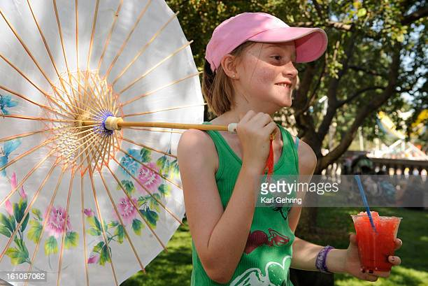 CD30TASTECO Ashlyn Hudson age 11 from Fort Collins enjoyed a cherry slushie in the shade of her new parasol Saturday afternoon Thousands of hungry...