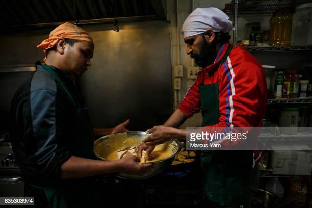 Ashok Kumar, left and Raj Kumar, right, prepare breakfast at the Shri Guru Ravidass, a Sikh temple that has opened its doors for all evacuees of the...